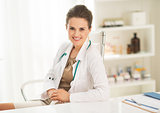 Portrait of happy medical doctor woman sitting in office
