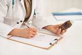 Closeup on medical doctor woman writing prescription