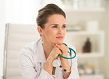 Portrait of thoughtful medical doctor woman sitting in office