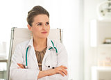Medical doctor woman sitting in office and looking on copy space