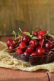 fresh red ripe cherries in wicker basket on a wooden table