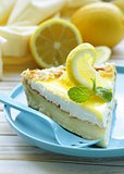 piece of lemon cake tart decorated with fresh lemon and mint