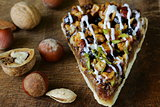 piece of pecan pie tart with various nuts on a wooden board
