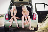 Two beautiful blond girls sitting in trunk of broken car