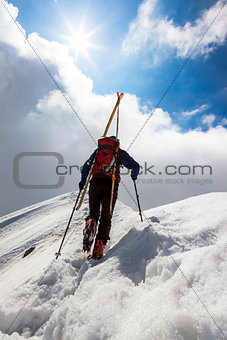 Ski mountaineer walking up along a steep snowy ridge with the s