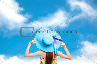 back of  girl holding a hat with blue sky background