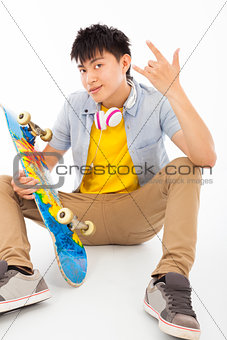 skateboard man sitting and make a rock gesture