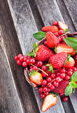 Fresh strawberry and redcurrant in a basket