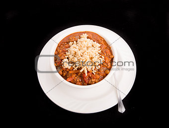 Bowl of Chili Over Rice on Black Background