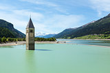 The bell tower in Reschensee and family (Italy).