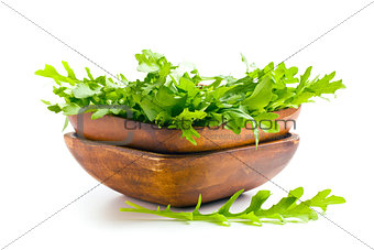 arugula leaves in wooden bowl