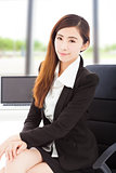 young confident businesswoman sitting in her office