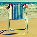 deckchair and orange flip-flops on the beach, with a retro effec