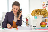 Fashion designer talking phone in office