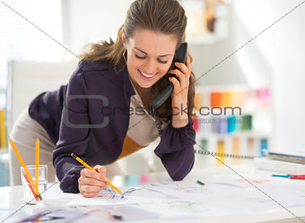 Smiling fashion designer in office talking phone