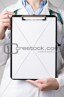 Doctor showing blank clipboard