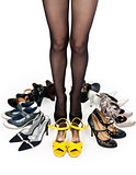 female legs in pantyhose, surrounded by stylish shoes