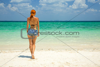 Beautiful redhead woman on the tropical beach
