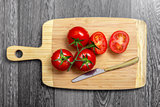 Top view of fresh tomatoes and knife on chopping board