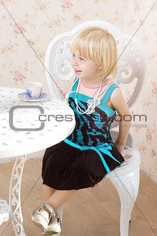 Little girl in a beautiful dress  drinking tea