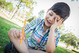 Frustrated Cute Young Boy Holding Pencil Sitting on the Grass