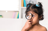 Cute Indian girl peeking through magnifying glass.