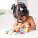 Indian girl zoom into toys through a magnifying glass