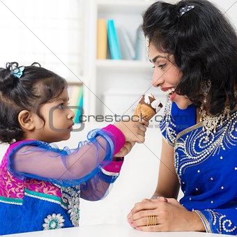 Indian girl feeding her mum ice-cream.
