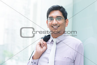 Indian business man leaning on modern building