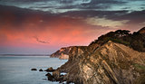 Beautiful vibrant sunrise over rocky coastline