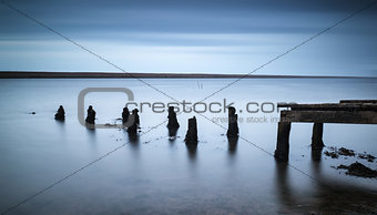 Long exposure landscape of old derelict jetty extending into lak