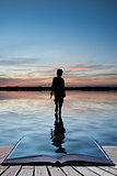 Book concept Concept image of young boy walking on water in suns