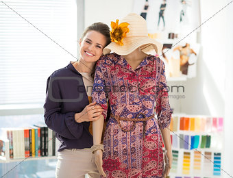Portrait of happy fashion designer with mannequin