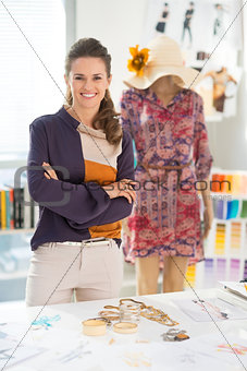 Portrait of smiling fashion designer in front of mannequin