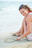 Happy young woman sitting on beach and drawing on sand
