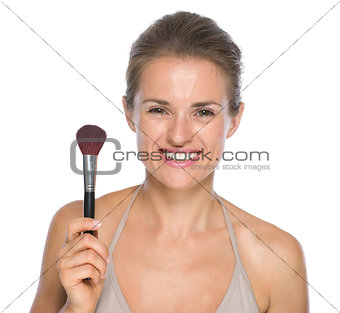 Portrait of smiling young woman showing makeup brush