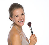 Portrait of smiling young woman with makeup brush