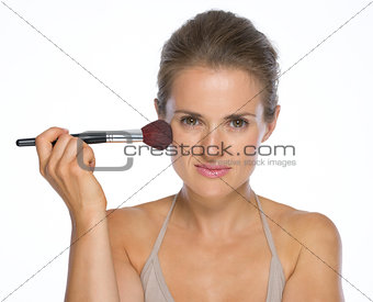 Portrait of young woman using makeup brush