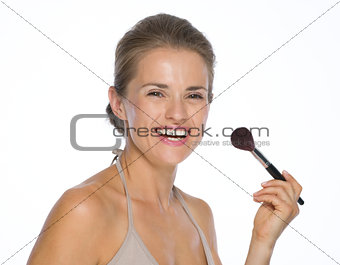 Portrait of happy young woman with makeup brush