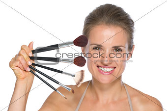 Portrait of happy young woman with makeup brushes
