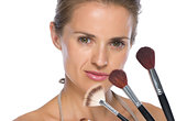 Portrait of young woman with makeup brushes