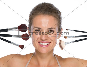 Portrait of smiling young woman with makeup brushes