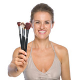 Closeup on smiling young woman showing makeup brushes