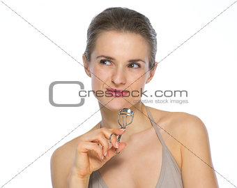 Portrait of young woman with eyelash curler looking on copy spac
