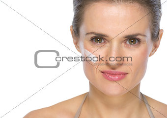 Portrait of young woman with creme on face