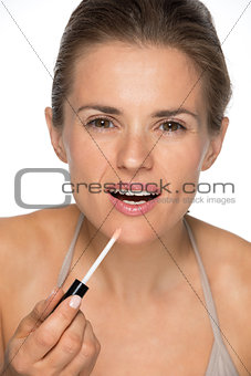 Portrait of happy young woman applying lip gloss