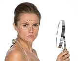 Concerned young woman with plastic surgery marks and mirror