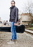 Handsome young man with guitar case in hand amongst industrial ruins