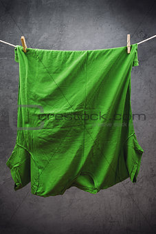 Green t shirt hanging on rope to dry