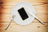 Mobile smart phone served as dinner on white plate